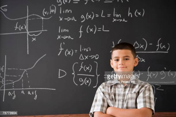 Hispanic boy smiling in front of math formula on blackboard