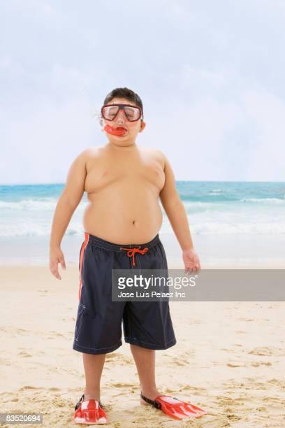 Hispanic boy standing at beach in snorkel gear