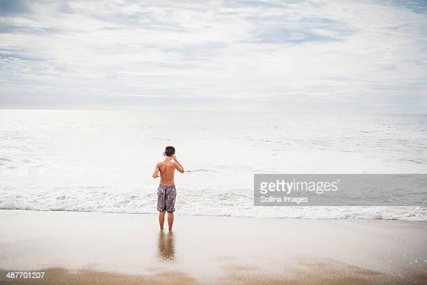 Hispanic boy standing in surf at beach