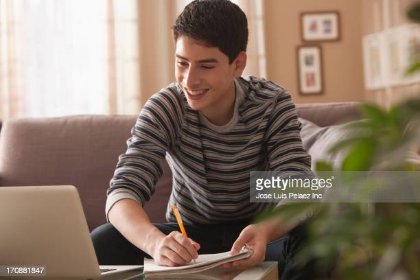 Hispanic boy studying on sofa