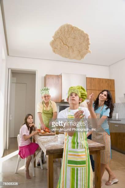 Hispanic boy throwing pizza dough