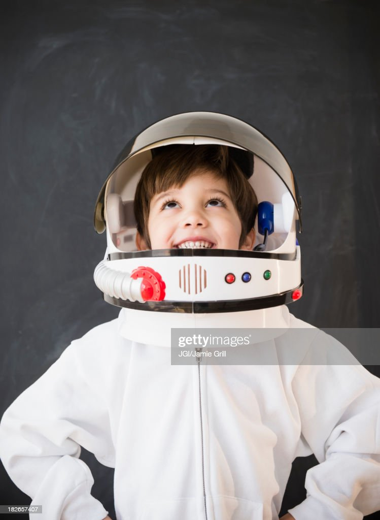 Hispanic boy wearing space helmet in classroom