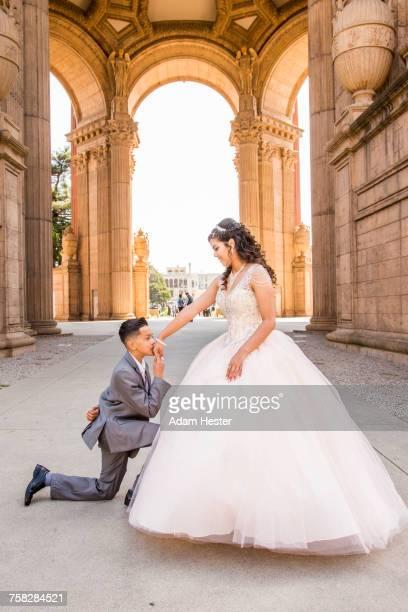 Hispanic boy wearing suit kissing hand of girl wearing gown