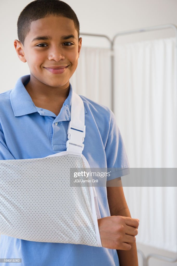 Hispanic boy with arm in sling : Stock Photo
