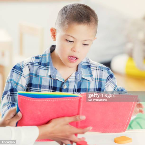 Hispanic boy with Down Syndrome reads book with unrecognizable teacher