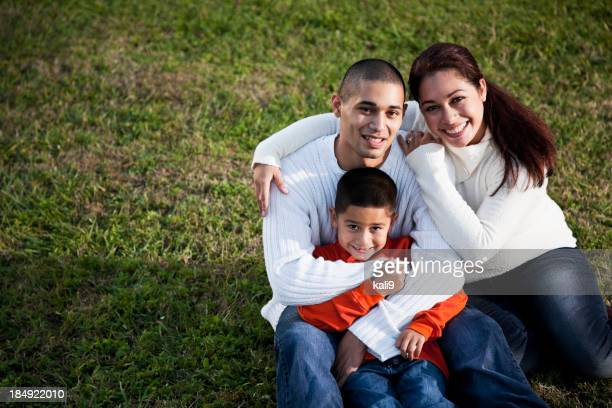 Hispanic boy with parents on grass