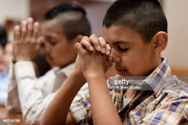 Hispanic boys praying in church