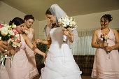 Hispanic bride and bridesmaids looking at dress
