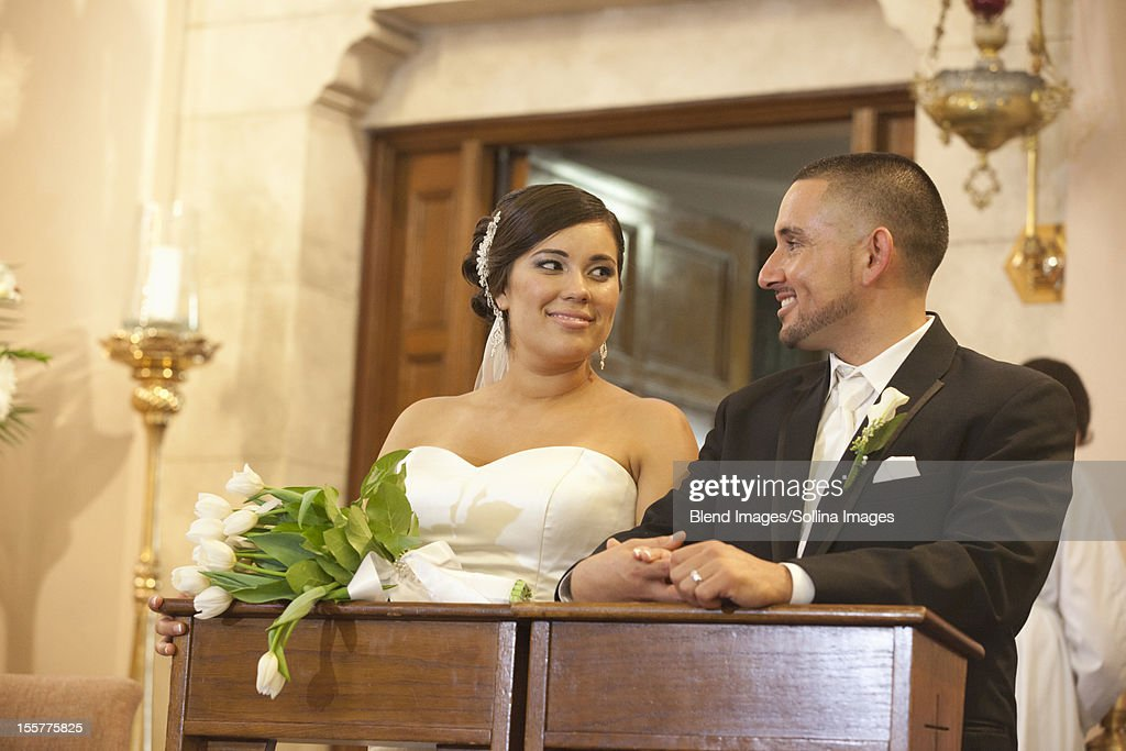 Hispanic bride and groom in wedding ceremony