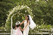 Hispanic bride and young girl dancing in circle