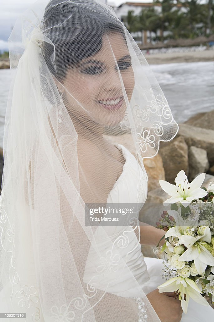 Hispanic bride in wedding dress : Stock Photo