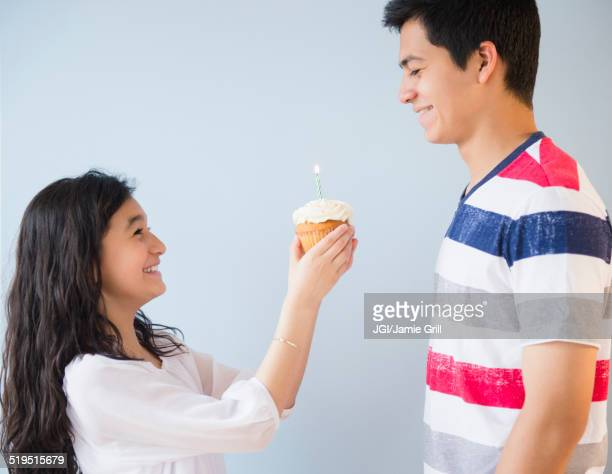 Hispanic brother and sister celebrating birthday with cupcake