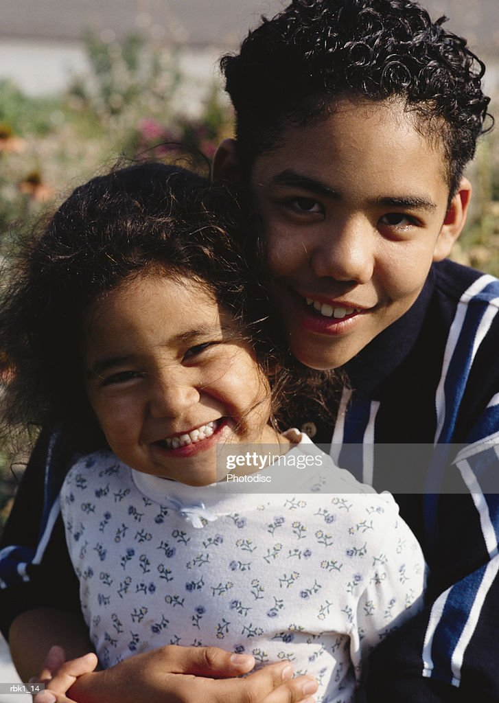 A hispanic brother and sister cuddle together and smile : Stock Photo