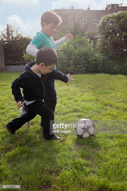 Hispanic brothers playing with soccer ball in backyard