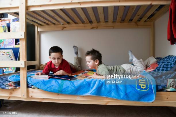 Hispanic brothers reading in bed