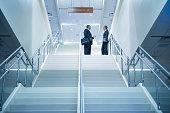 Hispanic business people talking on stairs