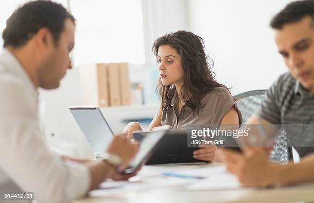 Hispanic business people using technology in office