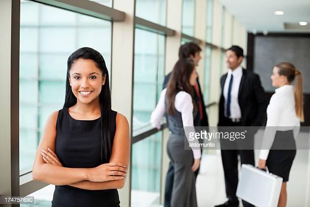 Hispanische business-Frau mit Ihren Kollegen im Hintergrund