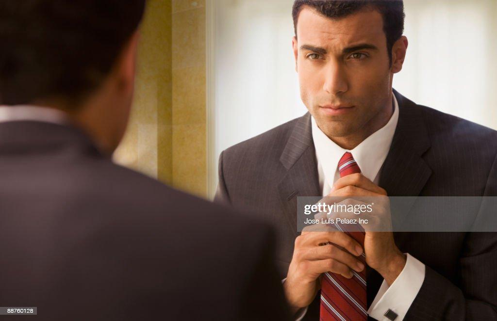 Hispanic businessman adjusting tie