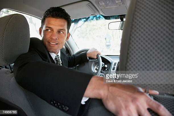 Hispanic businessman backing up car