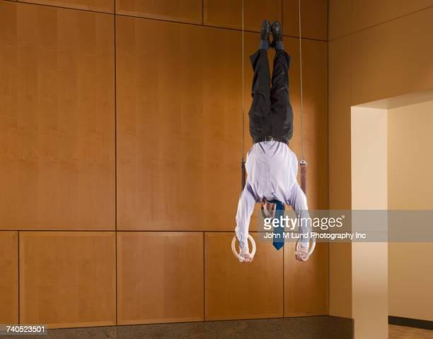 Hispanic businessman balancing upside-down on gymnastic rings