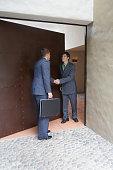 Hispanic businessman being greeted in doorway