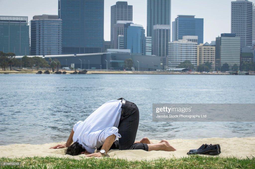 Hispanic businessman burying his head in sand on beach, Perth, Western Australia, Australia