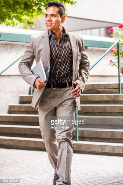 Hispanic businessman carrying digital tablet near staircase