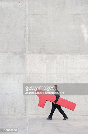 Hispanic businessman carrying large number 1