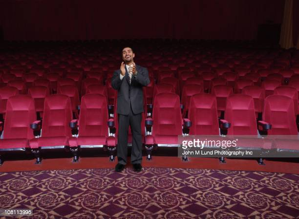 Hispanic businessman clapping in empty theater