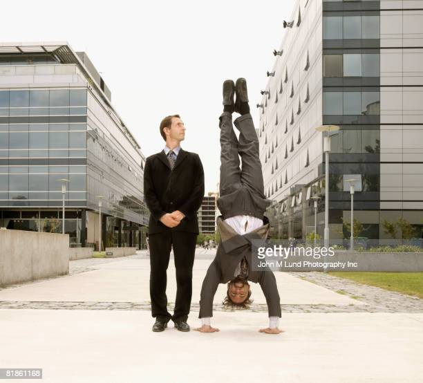 Hispanic businessman doing handstand next to coworker