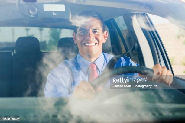 Hispanic businessman driving car