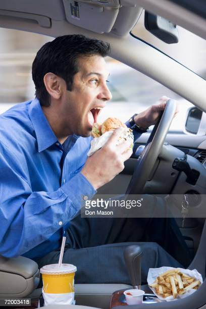 Hispanic businessman eating and driving
