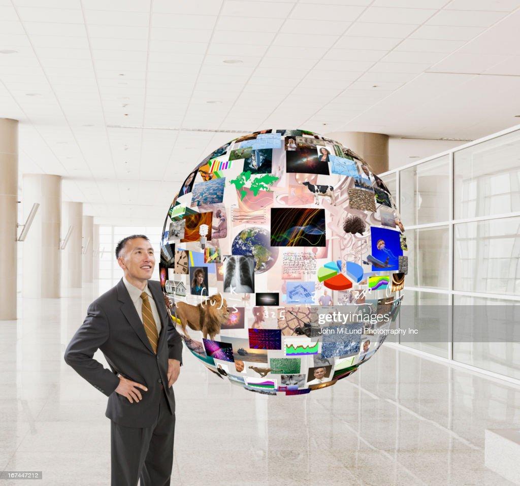 Hispanic businessman examining illustration of globe : Stock Photo