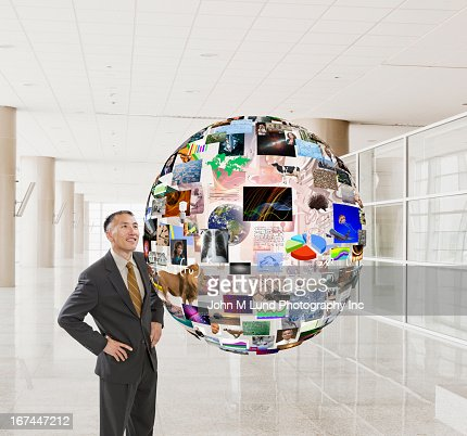 Hispanic businessman examining illustration of globe : Stock Photo