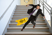 Mature Hispanic businessman falling down the stairs