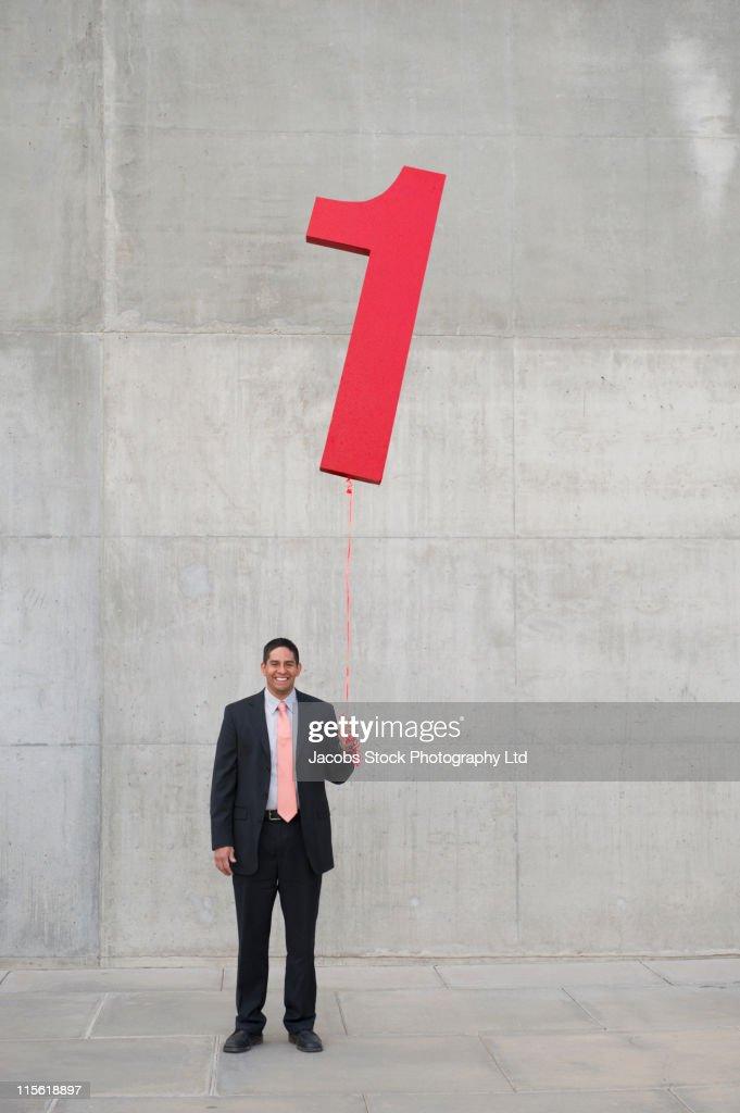 Hispanic businessman holding balloon shaped like number 1 : Stock Photo