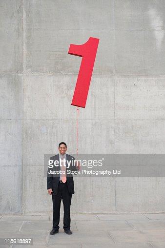 Hispanic businessman holding balloon shaped like number 1 : Foto de stock
