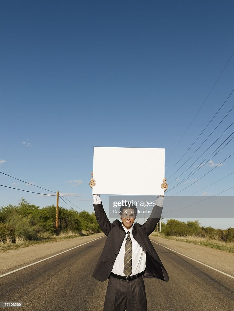 Hispanic businessman holding blank sign : Stock Photo