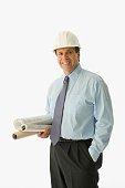 Hispanic businessman holding blueprints