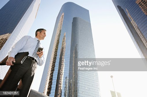 Hispanic businessman holding cell phone and notebook outdoors : ストックフォト