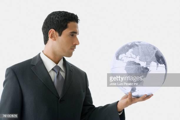 Hispanic businessman holding globe