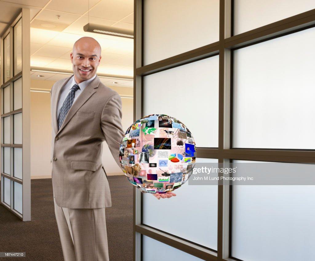 Hispanic businessman holding illustration of globe : Stock Photo