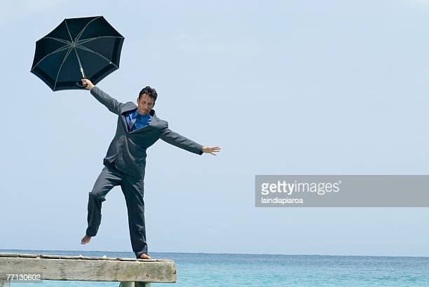 Hispanic businessman holding umbrella on dock