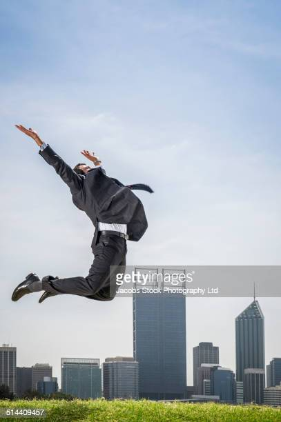 Hispanic businessman jumping for joy by Perth city skyline, Perth, Western Australia, Australia