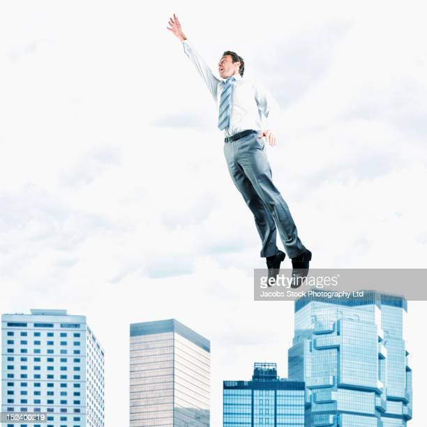 Hispanic businessman jumping in air