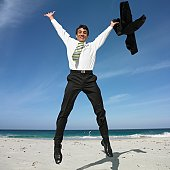 Hispanic businessman jumping on beach
