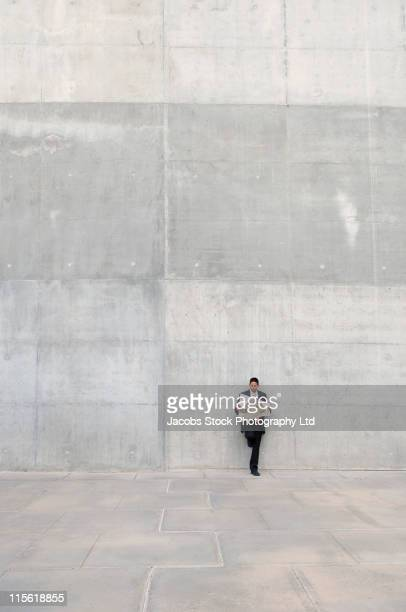 Hispanic businessman leaning on wall reading newspaper