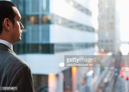 Hispanic businessman looking at city scene : Stock Photo