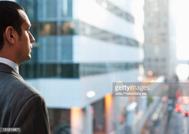 Hispanic businessman looking at city scene